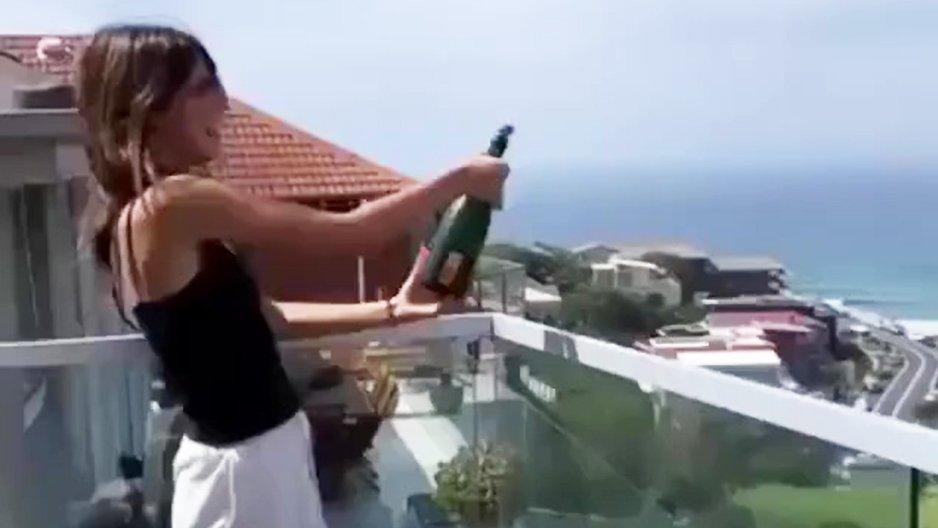 Une brune qui fait péter une bouteille de champagne
